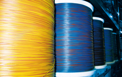 Blue and yellow automotive cables on large coils