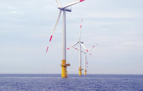 Three windmills at sea